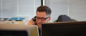 Man in office setting using telephone.