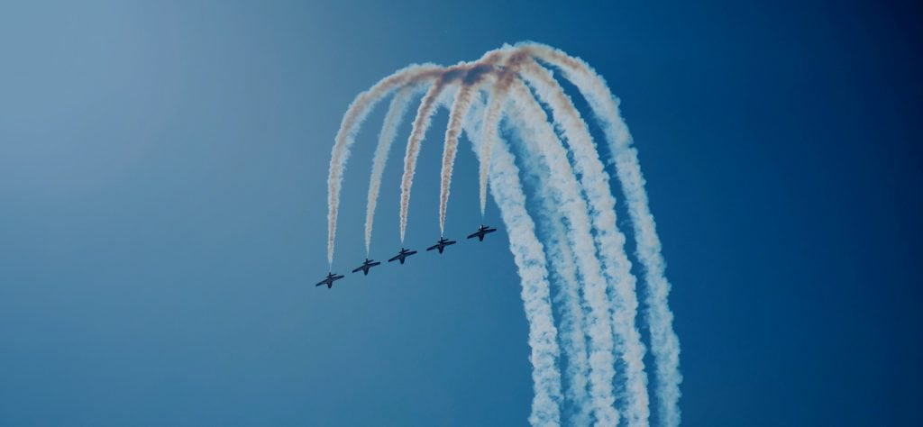 Five plane aerobatics team perform synchronised inside loop